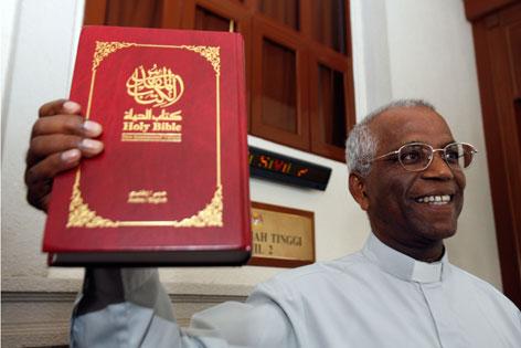 Ein malaysischer Priester mit einer arabischen Bibel