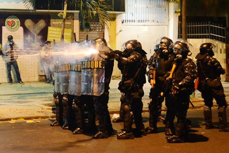 Polizisten in Einsatzmontur setzen Tränengas gegen Demonstranten ein