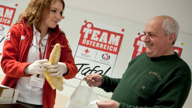 """Junge """"Team Österreich Tafel""""-Helferin übergibt Brot an einen älteren Mann"""