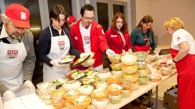 Team Österreich Tafel - Helfer hinter einem Tisch, auf dem Lebensmittel stehen