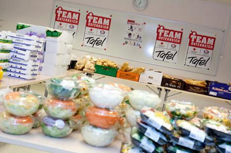 """Tisch mit Lebensmitteln, dahinter hängen Plakate mit dem """"Team Österreich Tafel""""-Logo"""