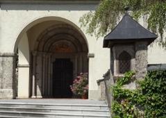 Das von grünen Sträuchern umgebene Eingangstor der Abtei.