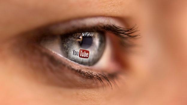 Das Youtube-Logo spiegelt sich im Auge einer Frau