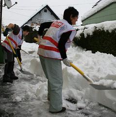 Team Österreich Mitglieder beim Schneeschaufeln
