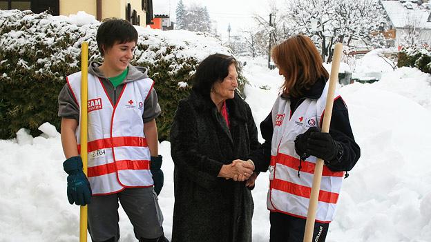 Frau dankt zwei Jugendlichen fürs Schneeschaufeln
