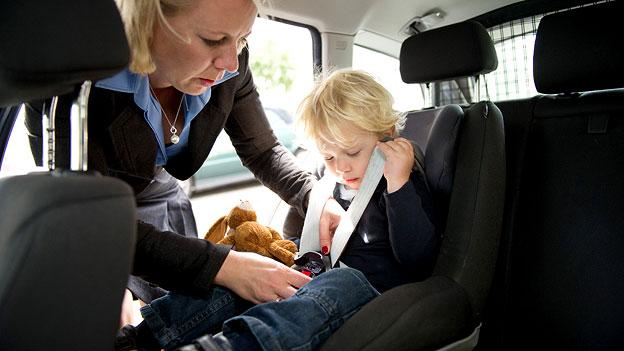 Eine Frau fixiert ihr Kind in einem Autokindersitz.