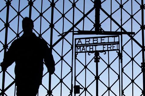 """Silhouette eines Mannes vor einem Gittertor mit dem Schriftzug """"Arbeit macht frei"""""""