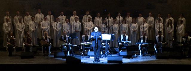 Sänger im Scheinwerferlicht, dahinter ein Chor
