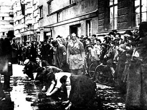 """""""Reibpartie"""" Wien 3, Hagenmüllergasse 15, März 1938. Juden werden gezwungen, die Straße von politischen Parolen zu säubern."""
