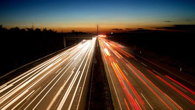 Autos auf der abendlichen Autobahn.