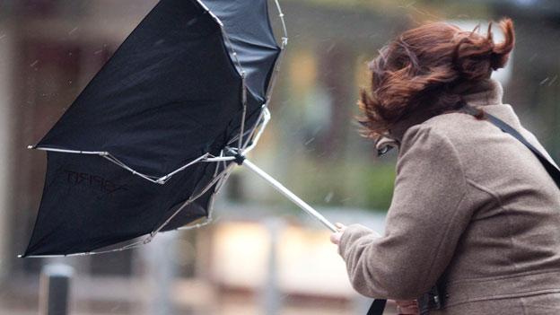 Eine Frau mit Regenschirm im Sturm