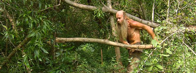 Mann mit langem Bart und nacktem Oberkörper schleppt einen großen Ast durch den Dschungel