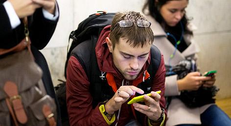 Wartende Öffipassagiere beschäftigen sich mit ihren Smartphones.