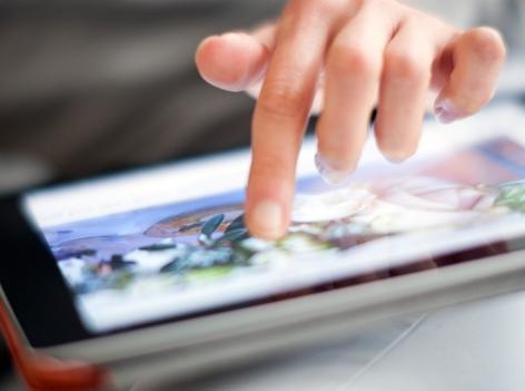 Eine Frauenhand tippt auf einem Tablet