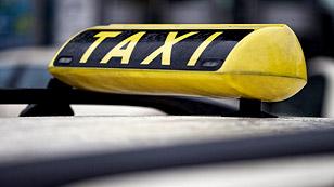Ein Taxischild auf einem Autodach.