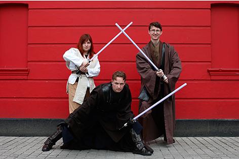 Zwei Männer und eine Frau als Jedi-Ritter mit Lichtschwertern verkleidet