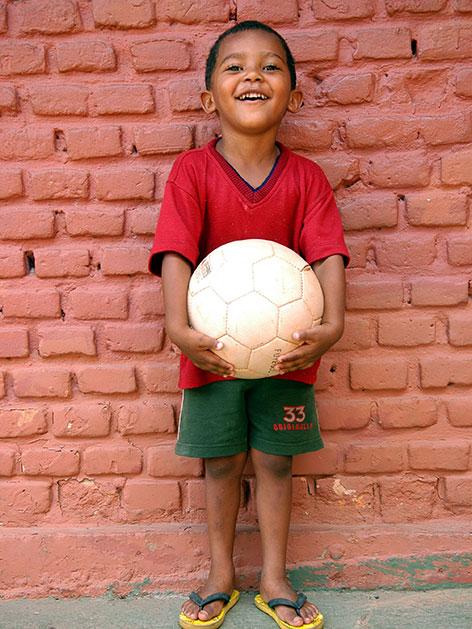 Ein kleiner Bub vor einer Ziegelmauer mit einem Fußball in der Hand