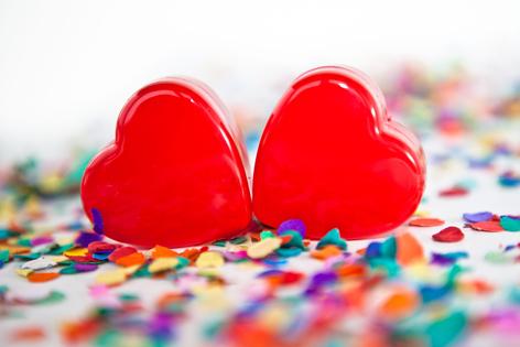 Zwei rote Herzen auf buntem Konfetti
