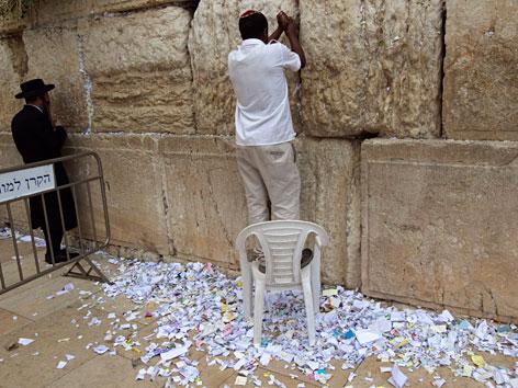 Ein Arbeiter entfernt Zettel aus der Klagemauer.