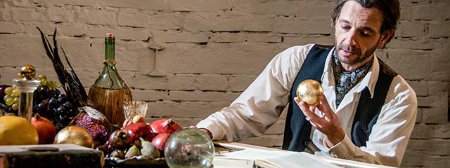 Mann mit Bart hält goldene Kugel in der Hand