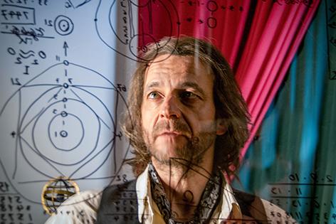 Mann mit Bart schaut auf wissenschaftliche Aufzeichnungen