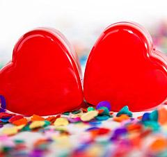 Zwei Herzerl liegen auf Konfetti