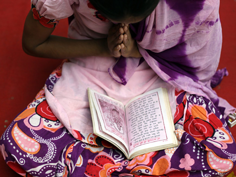 Indische Frau betet über einem Buch