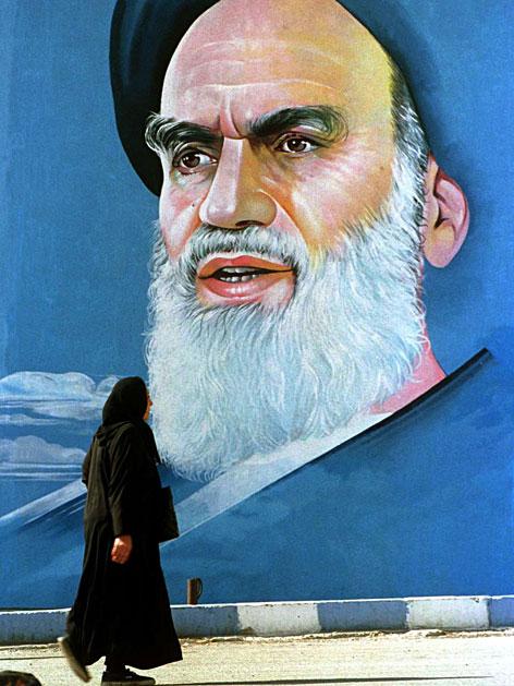 Eine Frau geht an einem Portrait von Ayatollah Khomeini vorbei.