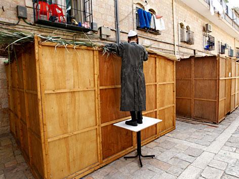 Ein orthodoxer Jude baut eine Laubhütte in Mea Schearim in Jerusalem