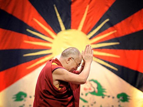 Der Dalai Lama vor einer tibetischen Flagge