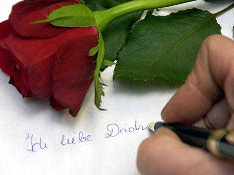 """Eine Hand mit Füllfeder schreibt """"Ich liebe Dich"""". Auf dem Briefpapier liegt eine rote Rose"""