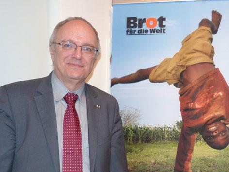 """Michael Bünker, Bischof der evangelischen Kirche A.B. in Österreich vor einem Plakat der Initiative """"Brot für die Welt"""""""