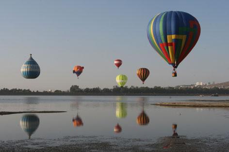 Heißluftballons fliegen über den Palote-Damm
