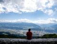 Ein Mann sitzt auf einer Mauer und betrachtet die Aussicht