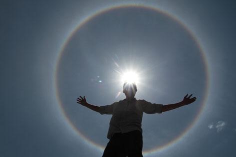 Ein Mann steht mit ausgebreiteten Armen vor der Sonne