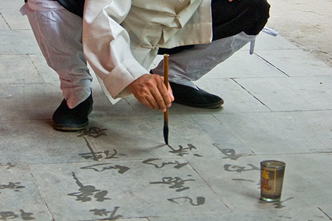 Mönch praktiziert Wasserkalligraphie auf Pflastersteinen