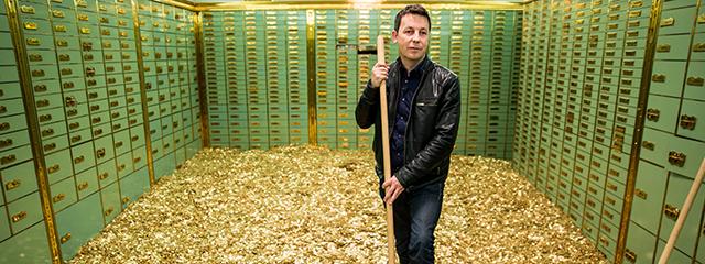 Mann mit Schaufel in Tresorraum, Boden mit einer Unzahl von Münzen bedeckt