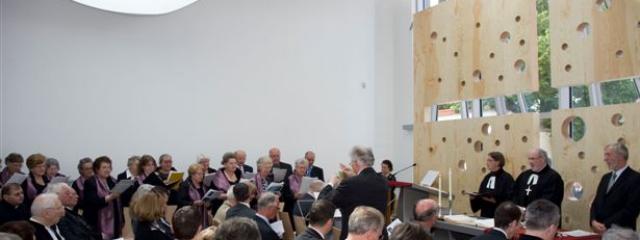 Gottesdienst in modernem Raum aus Beton und Glas und Holz mit Löchern an der Wand und einem Fenster in Kreuzesform gleich hinter dem Altar