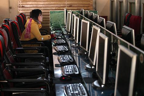 Junge Frau sitzt allein an einer Tischreihe mit Computern