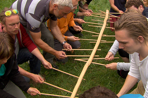 Männer bei einem Kooperationsspiel - mit kleinen Stäbchen muss ein größeres in der Mitte hochgehalten werden