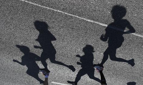 Marathonläufer als Schatten auf dem Asphalt