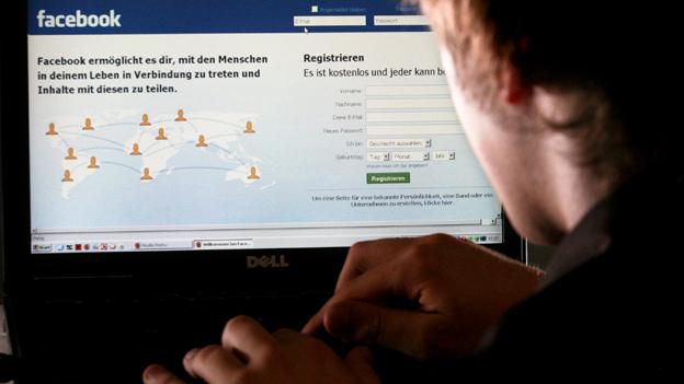 Ein junger Mann sitzt an einem Computer und surft im Internet