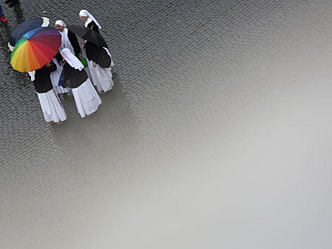 Klosterschwester mit buntem Regenschirm