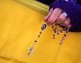 Eine Frauenhand hält einen Rosenkranz