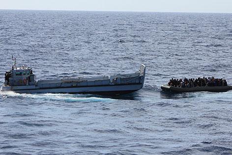 Ein Boot mit Flüchtlingen im Meer, daneben ein Rettungsschiff
