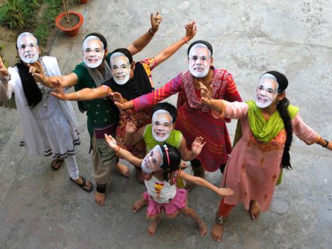 Anhänger der indischen BJP-Partei feiern den Wahlsieg mit Narendra-Modi-Masken