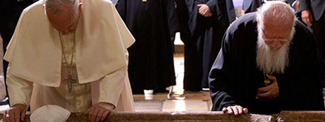 Papst Frnaziskus und Patriarch Bartholomaios knien in der Grabeskirche