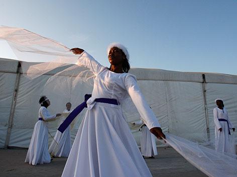 Eine weiß gekleidete Frau tanzend vor einem weißen Zelt