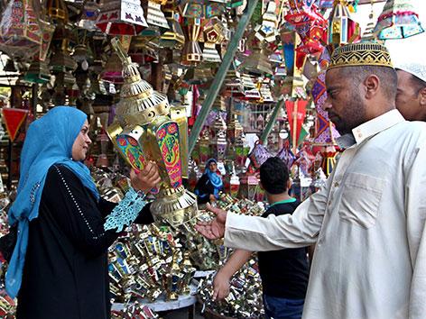 Eine Frau kauft auf einem Markt in Ägypten eine Lampe zur Dekoration für den muslimischen Fastenmonat Ramadan