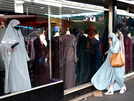 Verschleierte Frau mit Handy schaut in Auslage eines Modegeschäfts in Paris